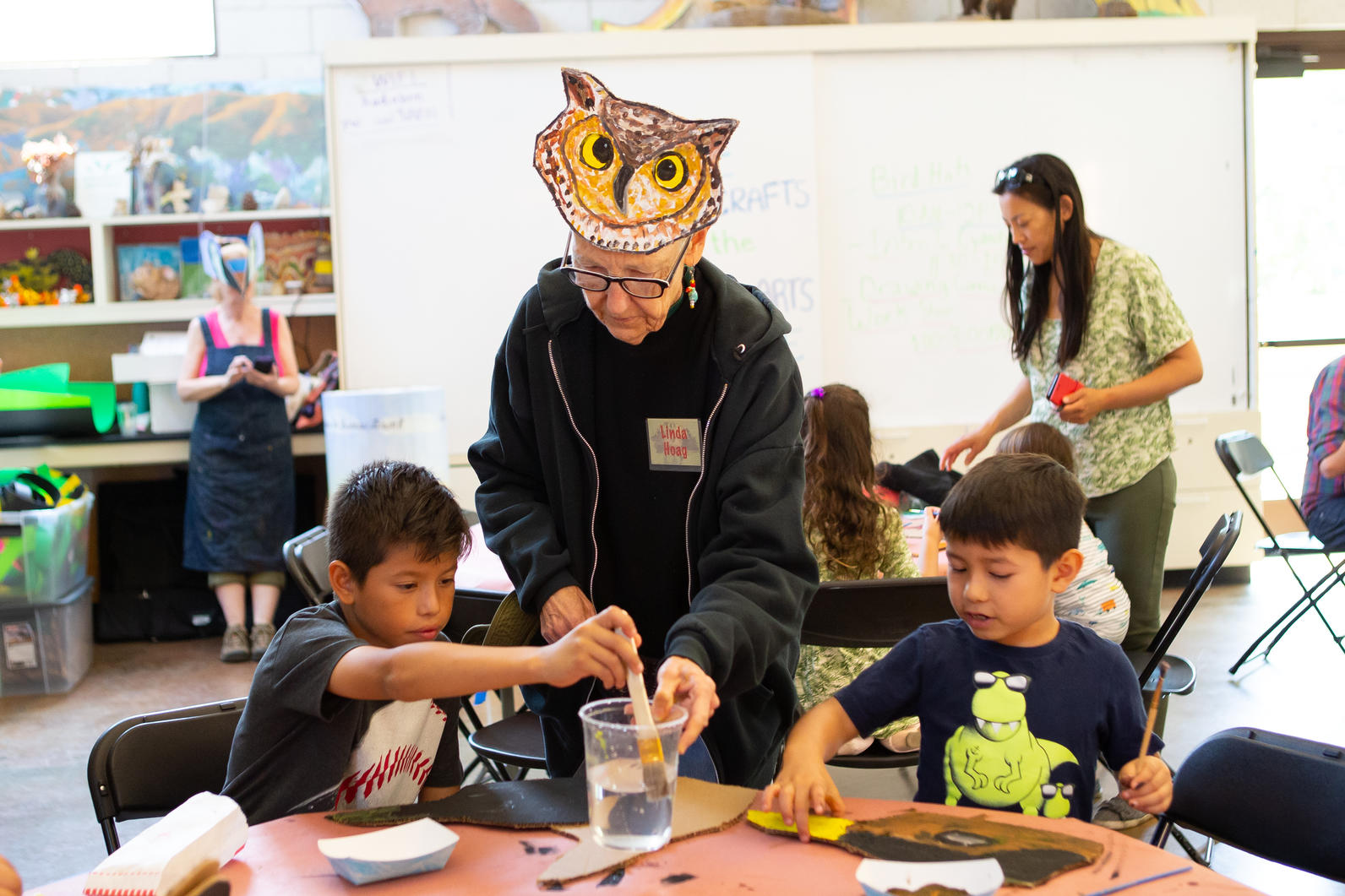 Member of Arroyo Arts Collective helps kids create bird hats in celebration of the Bird LA Day Festival.